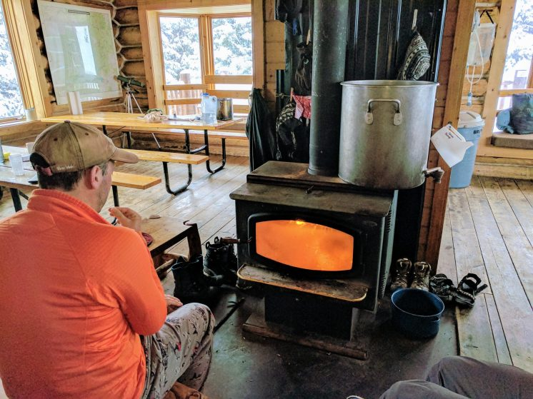 Man warms himself by a woodburning stove.