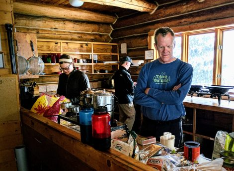 Man looks at coffee ingredients in a primitive kitchen.