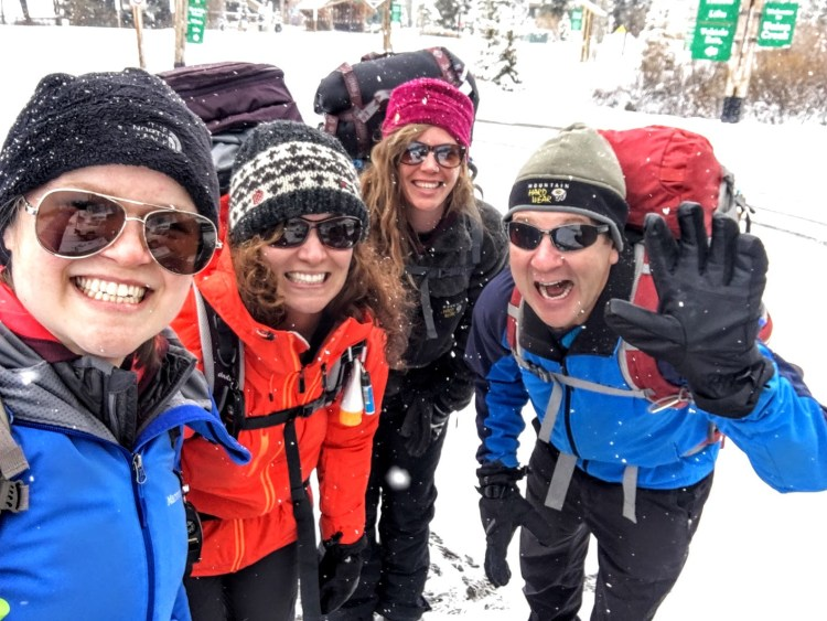 Four people dressed in winter outdoor gear on a snowy day.