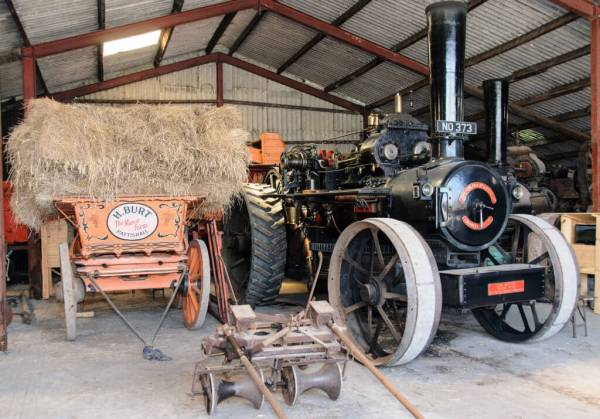 Black steam engine and vingtage hay cart