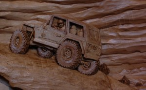 close up of a pictorial relief scene of a rock climbing jeep with mountains and clouds in the background