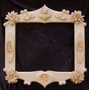 ornate frame incorporating large flowers, scrolls, angels relief carvings of little girls