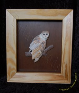 relief carving of a small barn owl in a shadow box frame