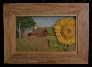 pictorial relief scene of a country landscape with a sunflower in the foreground and a barn in the background