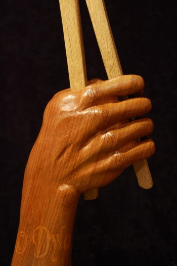 woodcarving of a hand holding tongs holding a horseshoe