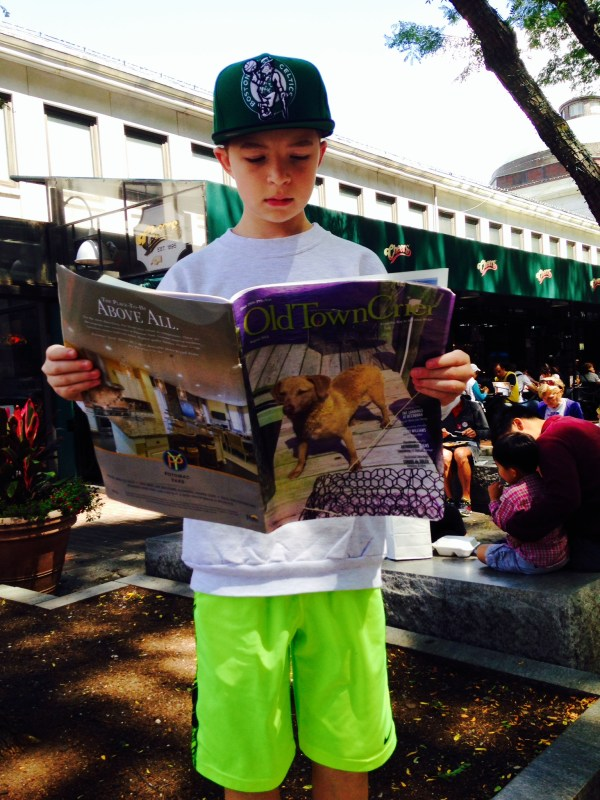 One of the Old Town Crier's youngest readers, Colby Morel, passes the time while waiting for a table with his father, Glen Morel, at the famous Cheers Bar in Boston, MA.