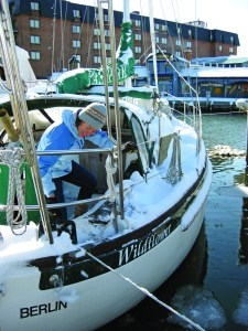 A liveaboard at Annapolis City Dock, Sarah shovels off her deck with a dust pan. She, her husband, another couple visiting from Germany, and their little boy hunkered down below for the blizzard of 2009 December 19. To read more about wintering aboard, turn to Tony Ireland's article on page 44 and the Editor's Note on page 10. Photo by Molly Winans/SpinSheet