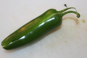 Cut the jalapenos in half lengthwise, including the stem.