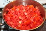 Freshly chopped tomatoes beginning to cook down on the stove