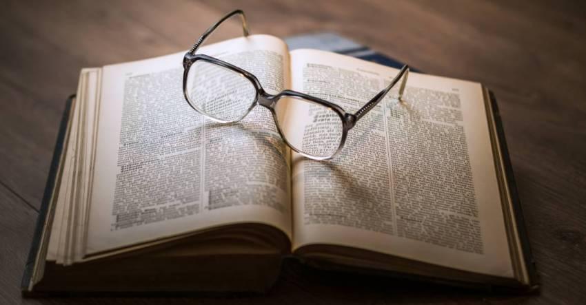 Раскрытая книга, очки, стол, фото