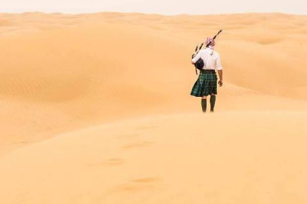 Escocês que viaja pelo mundo, caminhando pelo deserto com gaita de fole e kilt.