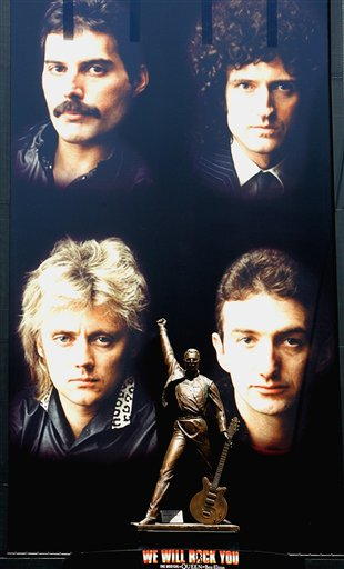 A bronze statue of Freddie Mercury, flanked by other members of the British rock group Queen, clockwise from top right, Brian May, John Deacon and Roger Taylor, looms over Japanese passersby at Tokyo's  entertainment district of Shinjuku on Sunday April 24, 2005. The 3-meter tall (9.9-foot) bronze statue of Mercury, who died in 1991, marks the Japanese tour next month of the British musical,