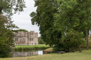 Looking through the trees and over the moat to the New Bield, from the garden labyrinth.