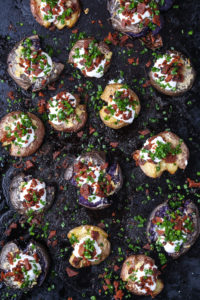 top-down shot of smashed potatoes, loaded with vegan toppings: butter, sour cream, bacon, chives