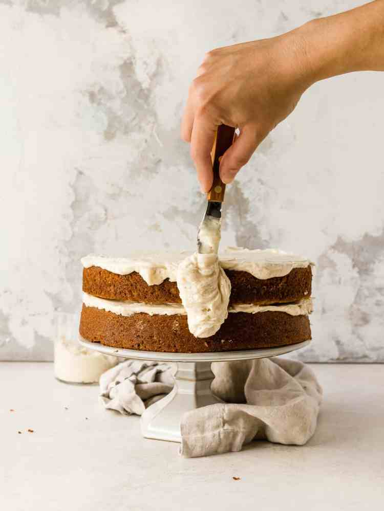 icing a cake with brown butter cream cheese buttercream