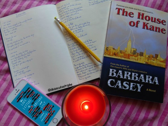 cover on phone and open notebook with burning candle
