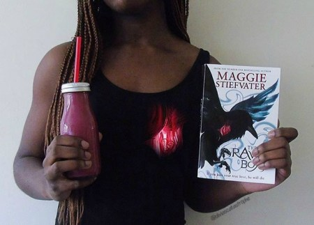 girl holding the raven boys with red smoothie on olivias catastrophe bookstagram