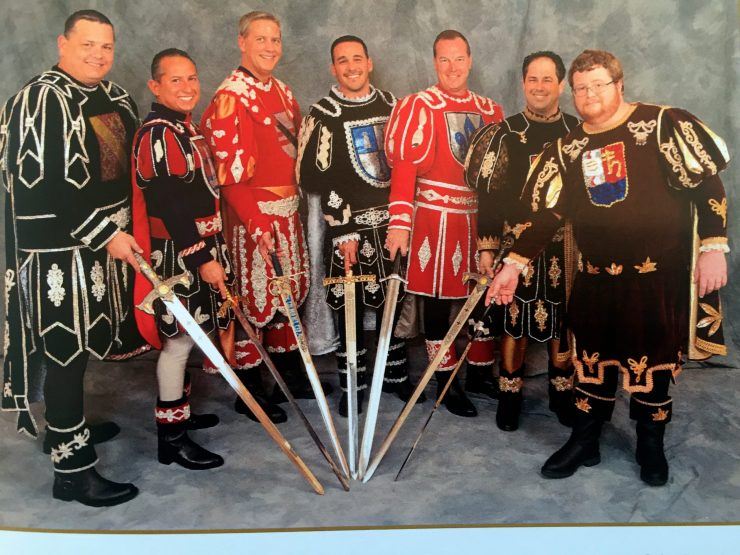 Seven men in costume holding swords