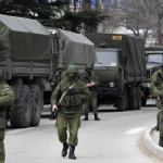 Armed servicemen wait near Russian army vehicles outside a Ukrainian border guard post in the Crimean town of Balaclava