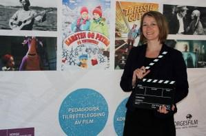 Tina Jensen står foran filmplakater i Norgesfilm.