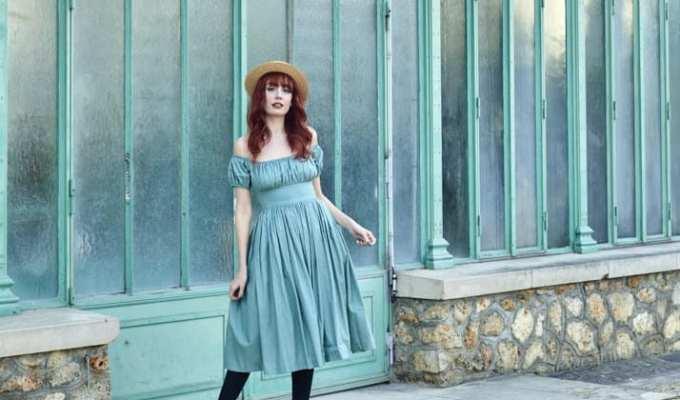 Photographie de Louise Ebel en robe devant un bâtiment vert
