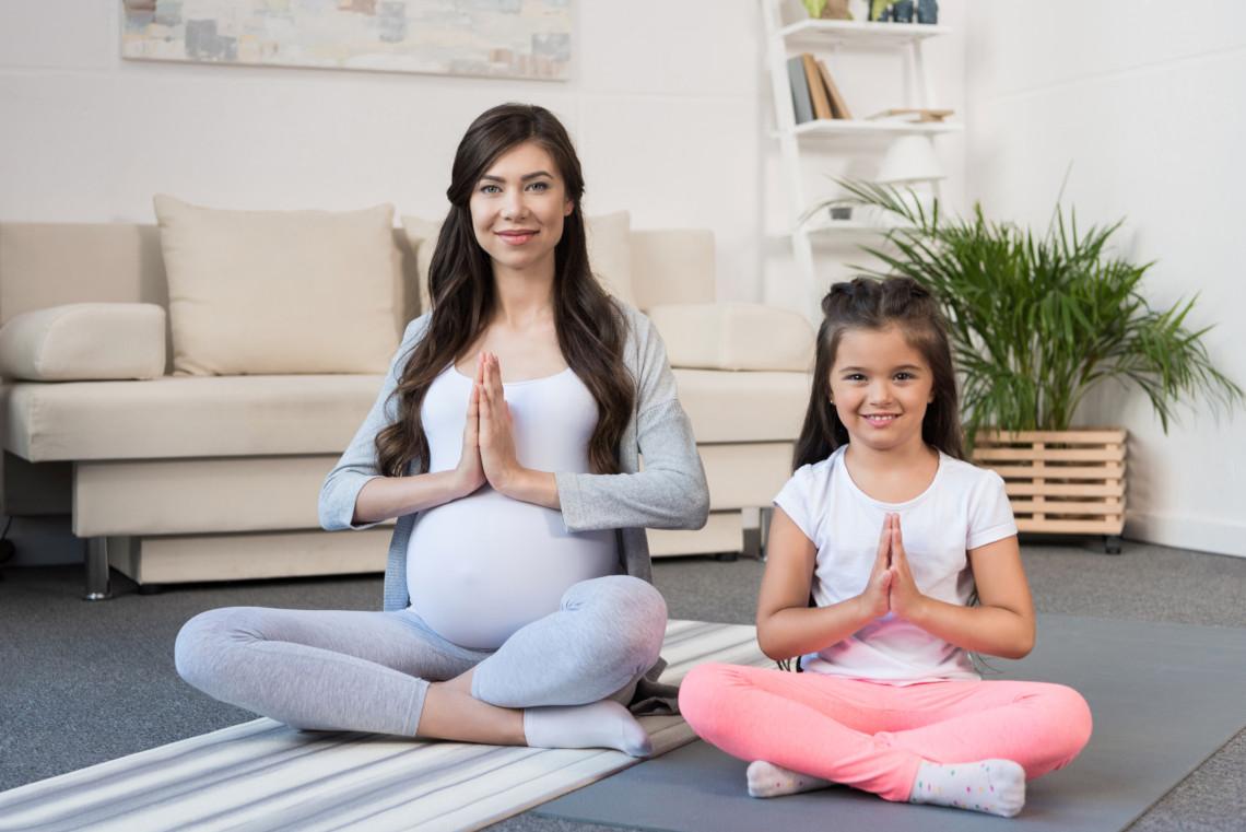 Une maman enceinte et sa fille en posture et tenue de Yoga. Elles semblent méditer dans leur salon.