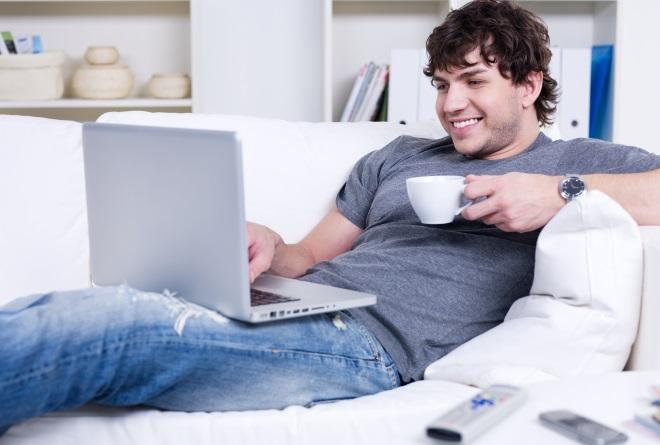 ラップトップを読んで笑顔の男