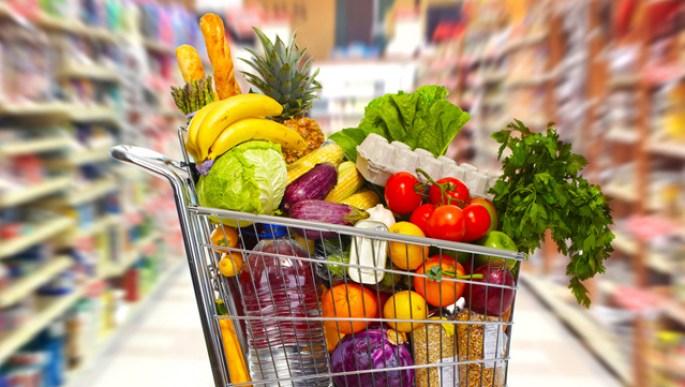 Chariot de courses plein de produits frais dans les rayons de supermarché ouvert dimanche