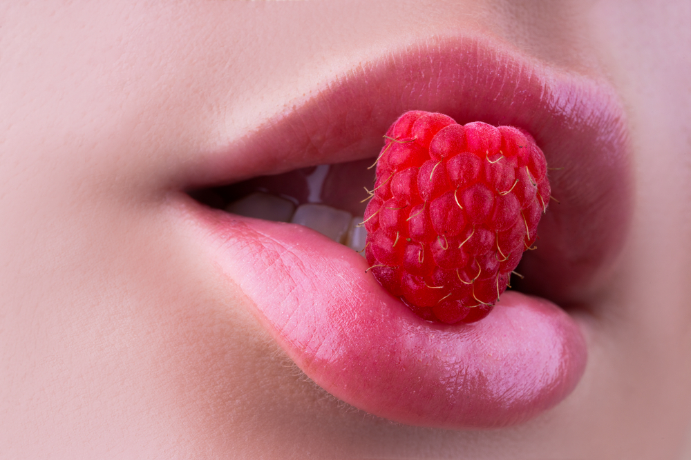 Framboise tenue entre les lèvres d'une jolie bouche de femme