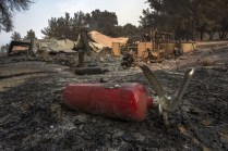 SANTA BARBARA, CA - JULY 09: A burned fire extinguisher is seen next to structures at Rancho Alegre Boy Scouts of America outdoor school that were destroyed by the Whittier Fire on July 9, 2017 near Santa Barbara, California. The Whittier Fire and the Alamo Fire together have blackened more than 30,000 acres of chaparral-covered hills in Ventura County. Statewide, about 5,000 firefighters are fighting 14 large wildfires. David McNew/Getty Images/AFP