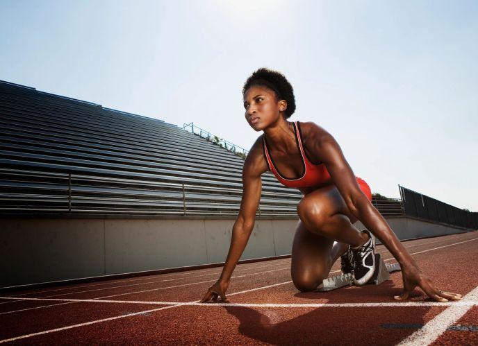 Mujer a punta de arrancar una carrera de pista