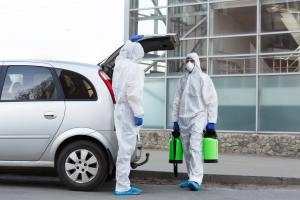 Man in hazmat suits buying disinfection spray for home cleaning