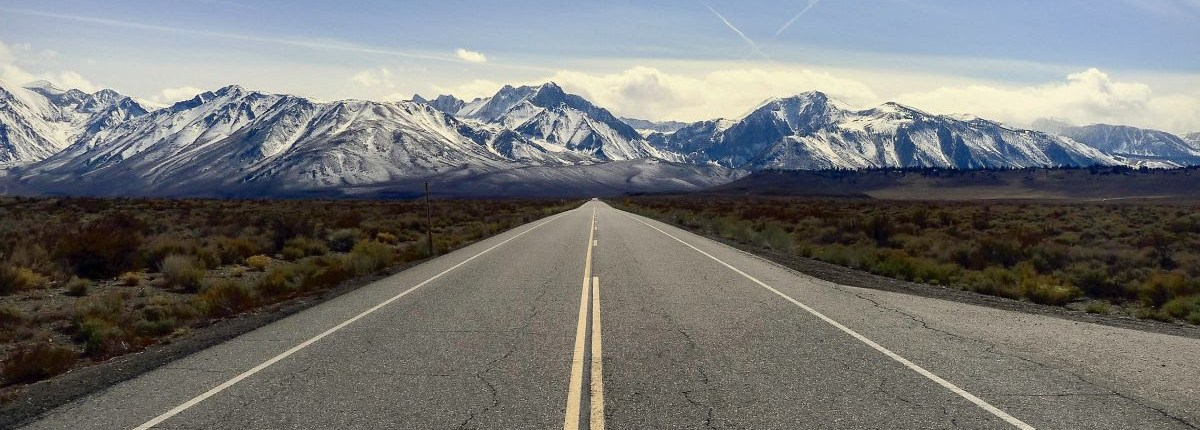 long road with mountians on the horizon