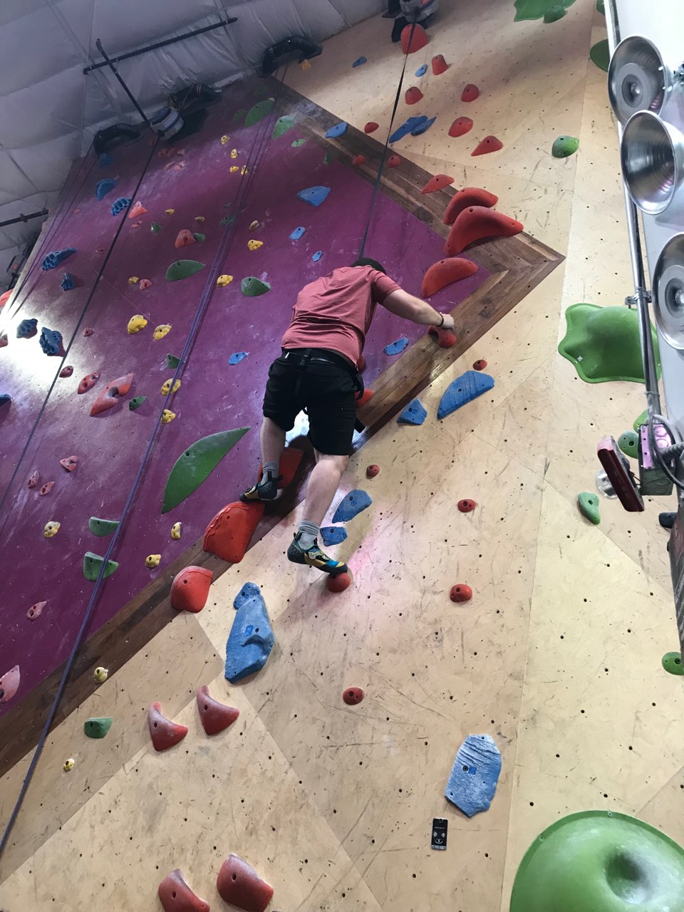 Photo of male client indoor rock climbing, on his way down the wall
