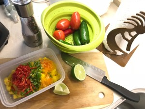 Chopped mango, orange, green and red peppers sit in container on cutting board with knife and sliced lime