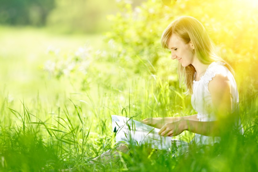 Young woman reading on nature.