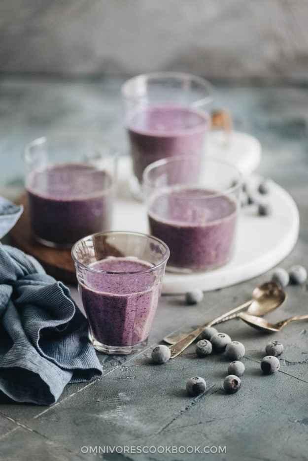 Blueberry banana smoothie with frozen blueberries garnish