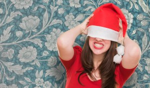 angry woman with a christmas hat covering her eyes against a vintage background