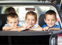 Three children and  mother in the car looking  and waving their hands,  as if saying goodbye to somebody while traveling for a vacation. Selective Focus, focus is on the girl