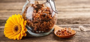 Propolis granule in glass jar on rustic wooden background
