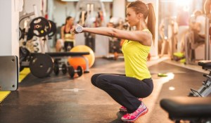 Young woman doing exercises with weights while being in squat position.