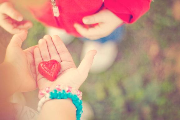 Little girl holding  little heart in her hands offering,sharing it with her friend.
