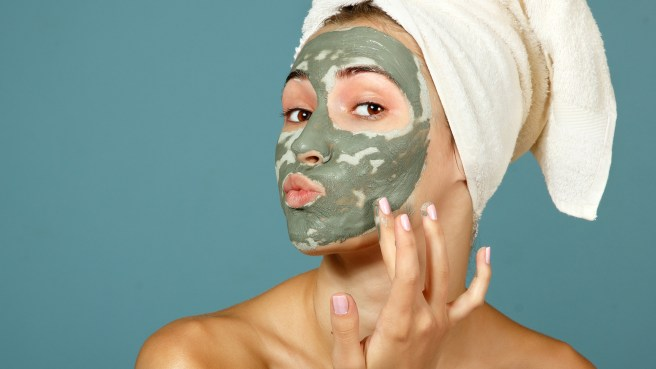 Spa teen girl applying facial clay mask. Beauty treatments. Over blue background.; Shutterstock ID 112909861