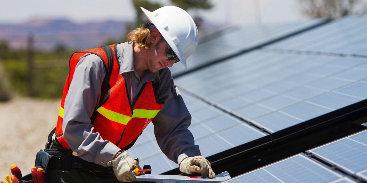 Projeto de eficiência energética: imagem de técnico avaliando painel solar