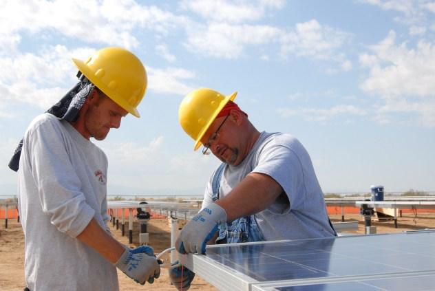 Instalação de sistema solar: operários instalando módulo fotovoltaico