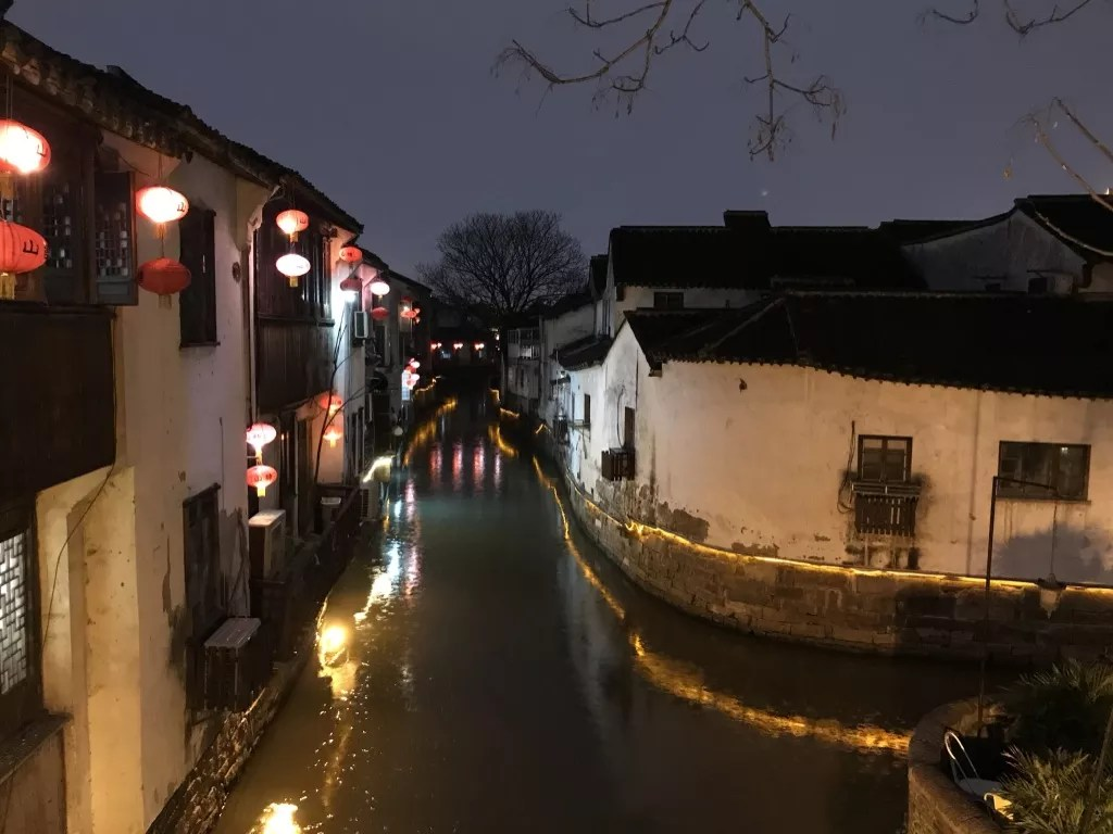 a canal in Suzhou, lit up in the evening.