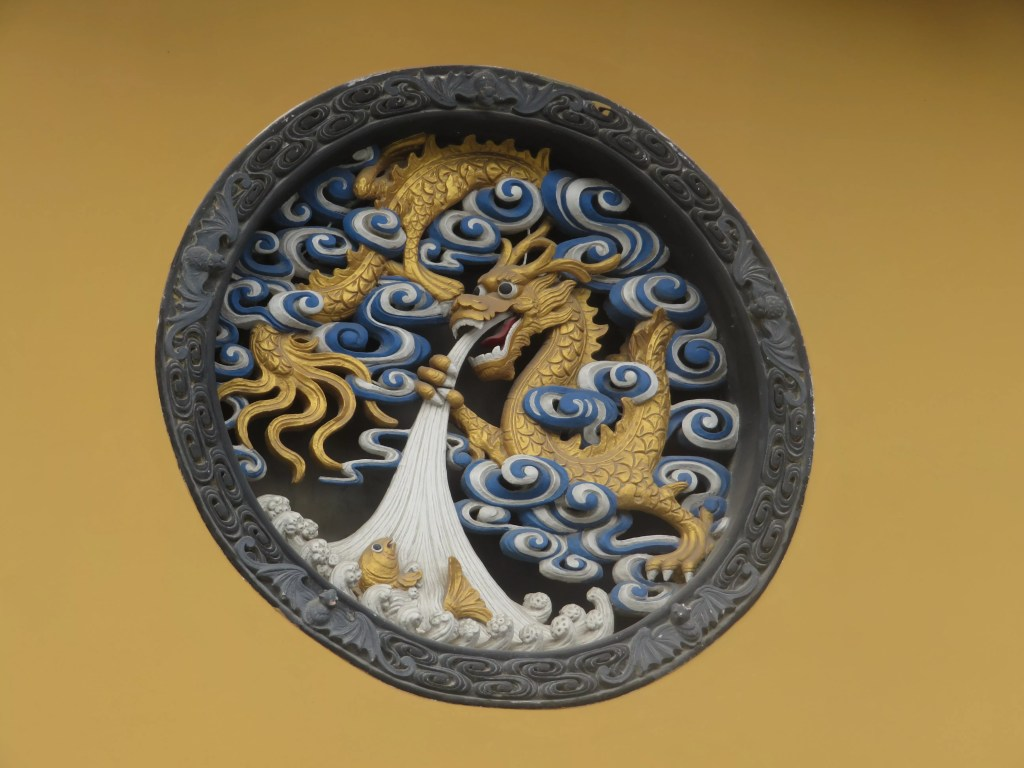 a carved chinese dragon in a yellow wall