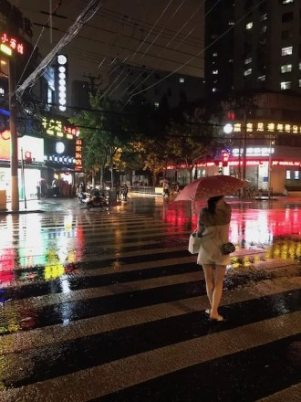 A woman walks in the rain in Shanghai - Is the water in China safe? onaroadtonowhere.com