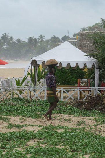 Un homme portant sur sa tête du sable pour aller le déposer dans une guesthouse