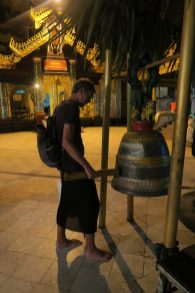 Julien fait sonner une cloche dans l'un des temples du complexe